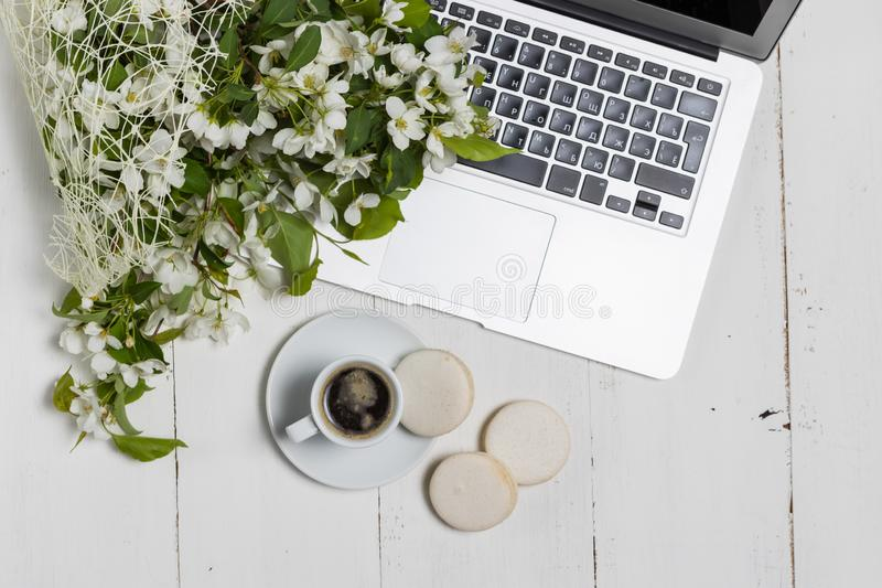 Het vrouwelijke bedrijfsconcept met laptop, de lente bloeit boeket en van de vrouw handen houdend kop van warme thee of koffie stock afbeeldingen