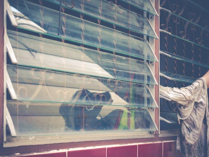Het vrouwelijke blinde glas van het hand schoonmakende venster royalty-vrije stock foto's
