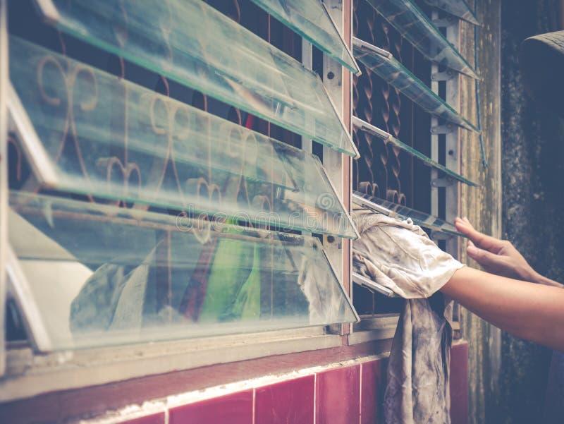 Het vrouwelijke blinde glas van het hand schoonmakende venster stock foto