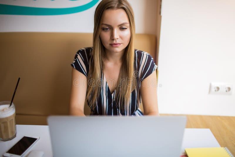 Het vrouwelijke blogschrijver intikken op netbook terwijl het zitten in koffiewinkel stock afbeelding