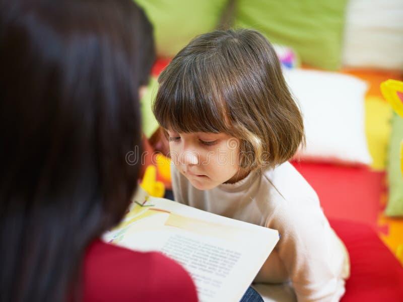 Het vrouwelijke boek van de leraarslezing aan meisje stock foto