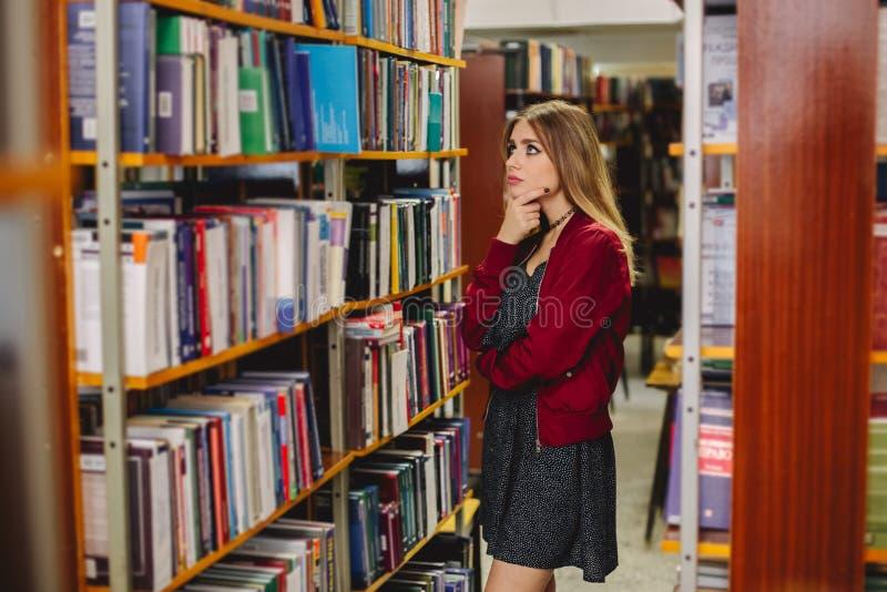 Het vrouwelijke boek van studentenchosinga in universiteitsbibliotheek Het concept van het onderwijs royalty-vrije stock afbeeldingen