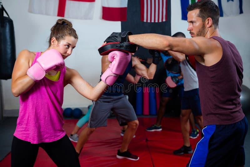 Het vrouwelijke bokser en instructeurs praktizeren met het in dozen doen stock foto's