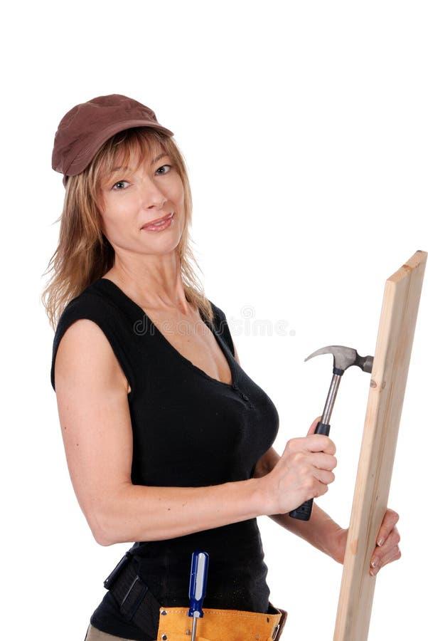 Het vrouwelijke bouwvakker hameren stock afbeeldingen