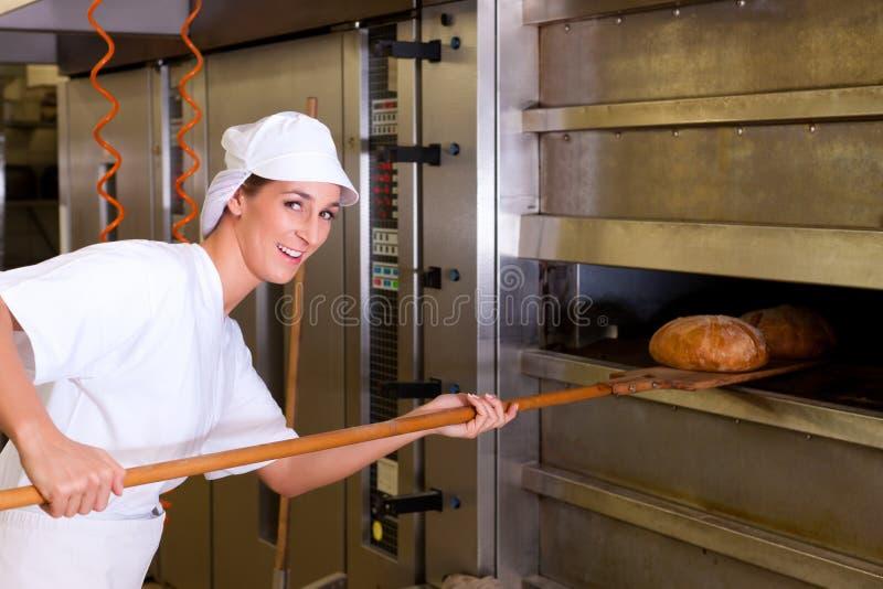 Het vrouwelijke brood van het bakkersbaksel stock foto