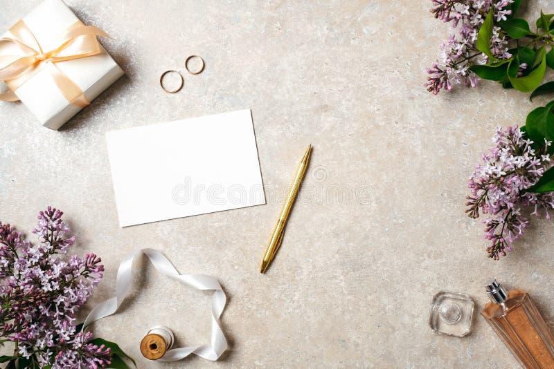 Het vrouwelijke bureau met huwelijkstoebehoren, lege document kaart, gouden pen, parfumfles, lint, ringen en de lentesering bloei stock afbeelding