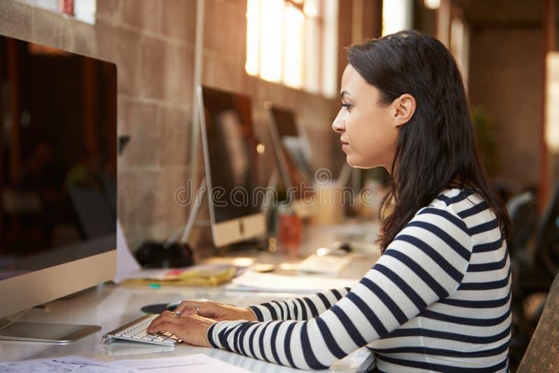Het vrouwelijke Bureau van Ontwerperusing computer at in Modern Bureau stock fotografie