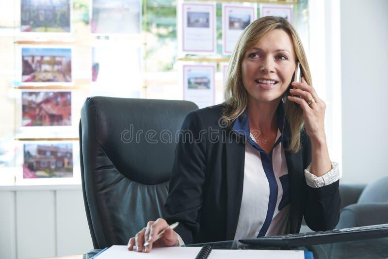 Het vrouwelijke Bureau van On Phone In van de Landgoedagent royalty-vrije stock fotografie
