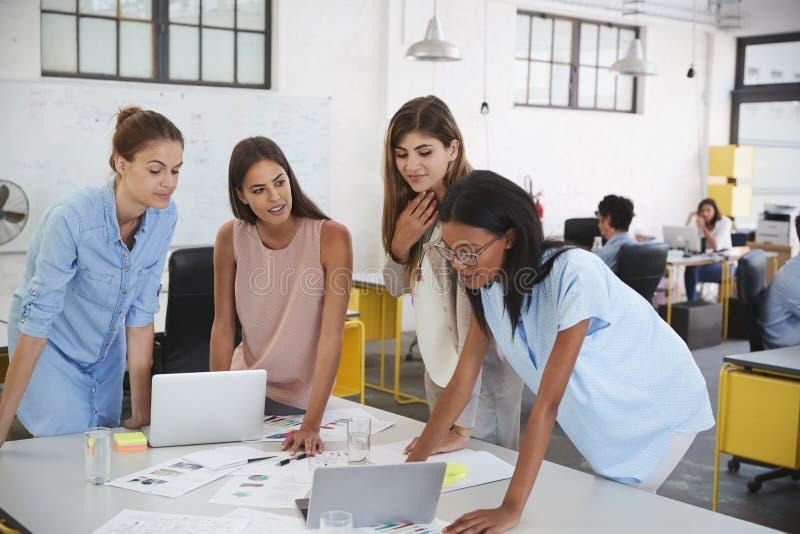 Het vrouwelijke commerciële teamwerk die zich bij bureau bevinden, sluit omhoog royalty-vrije stock afbeelding