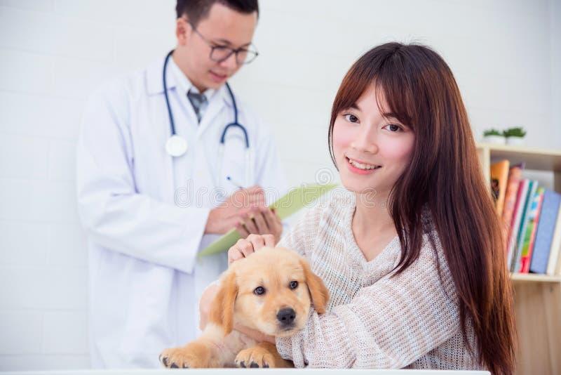 Het vrouwelijke eigenaar stellen met haar puppyhond het glimlachen royalty-vrije stock afbeelding