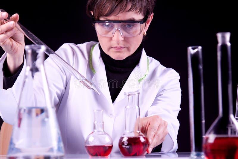 Het vrouwelijke experimenteren van de Wetenschapper stock foto's