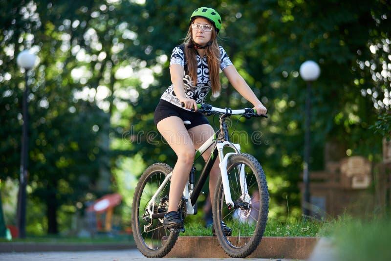 Het vrouwelijke fietser het berijden fiets denken aan toekomst stock fotografie