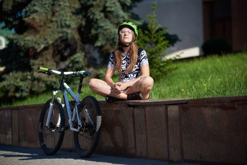 Het vrouwelijke fietser ontspannen na opleiding stock foto's