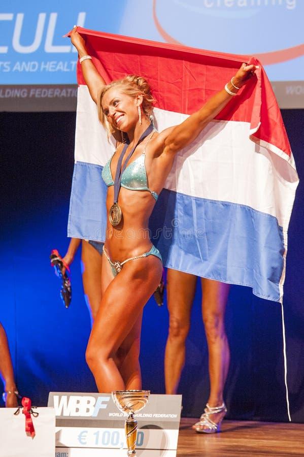 Het vrouwelijke geschiktheidsmodel viert haar overwinning op stadium met vlag royalty-vrije stock afbeeldingen