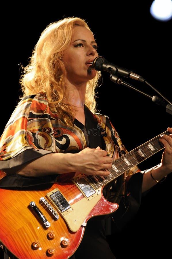 Het vrouwelijke gitarist spelen in lveoverleg stock afbeelding