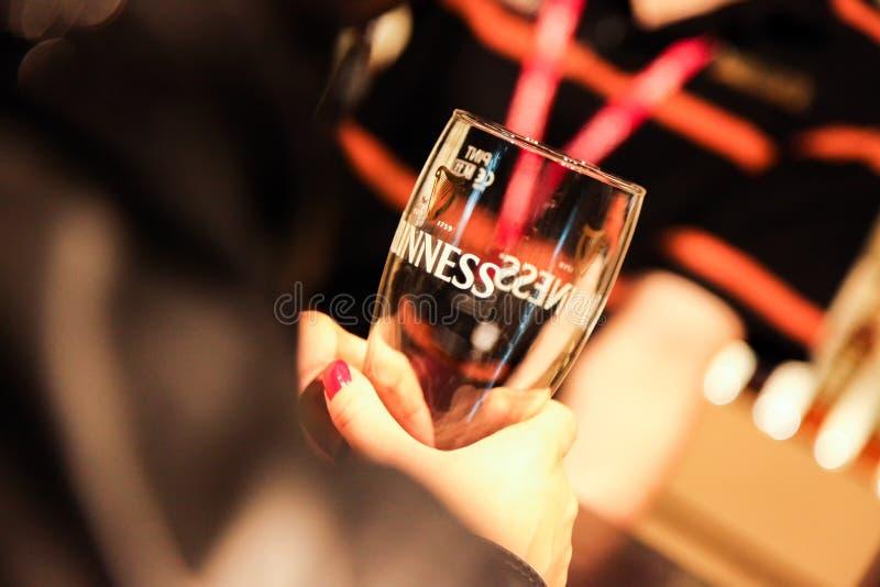 Het vrouwelijke glas van Guiness van de handholding bij Guiness-Pakhuisbrouwerij, Dublin stock afbeeldingen