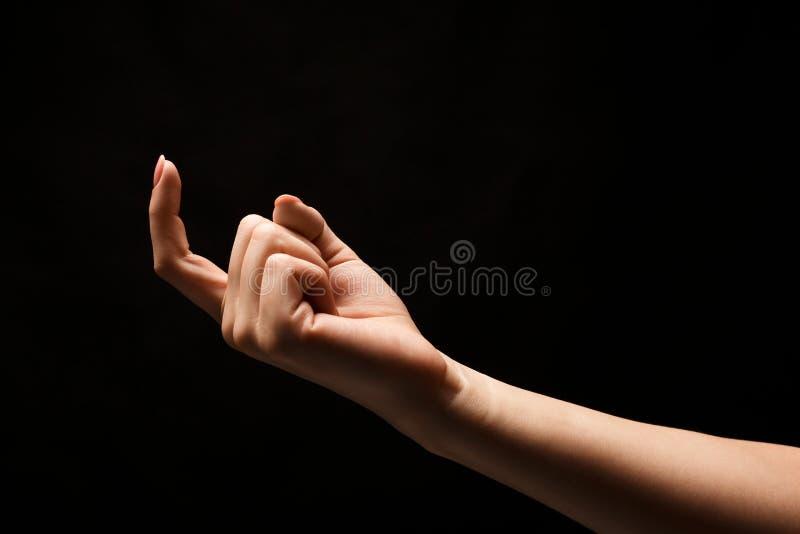 Het vrouwelijke hand wenken geïsoleerd op zwarte achtergrond stock afbeelding