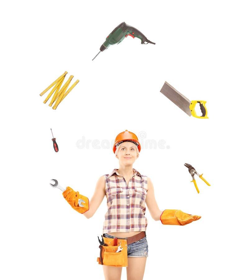 Het vrouwelijke handarbeider jongleren met met hulpmiddelen stock afbeelding