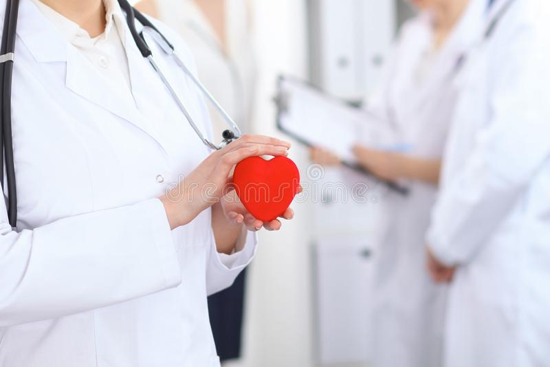 Het vrouwelijke hart van de artsenholding in haar handen Arts en geduldige zitting op de achtergrond Cardiologie in geneeskunde stock foto's