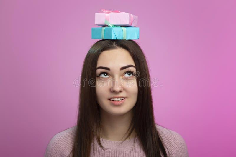 Het vrouwelijke hoofd met giftvakjes op haar hoofd, verrast meisje een stapel van stelt in decoratief document, conceptenvakantie royalty-vrije stock afbeeldingen