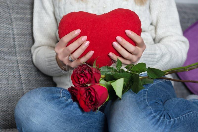 Het vrouwelijke hoofdkussen van het holdings grote rode hart ter beschikking op haar borst en zitting op bed en rozen op knieën stock foto