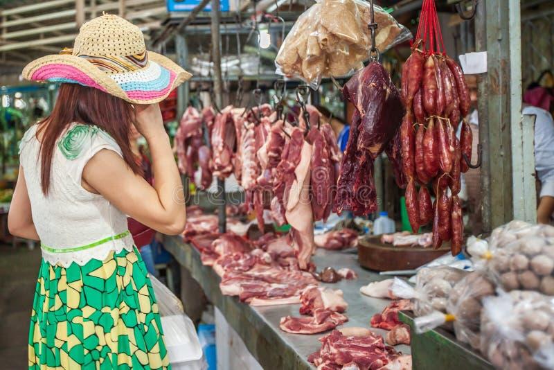 Het vrouwelijke klant het kopen vlees bij butcher's winkelt, verscheidenheid van vlees, varkensvlees, rundvlees, kip, ribben en royalty-vrije stock foto's