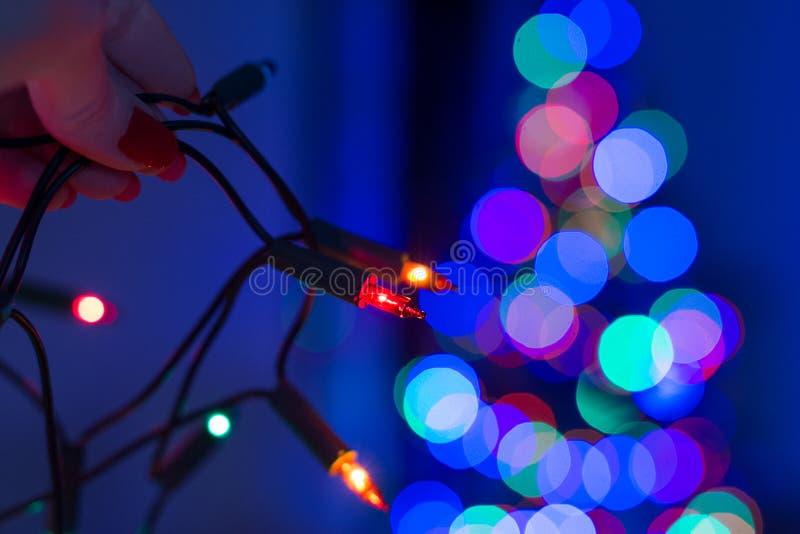 Het vrouwelijke koord van de handholding van Kerstmislichten met defocused Kerstmisboom op de achtergrond De Lichten van Kerstmis royalty-vrije stock foto