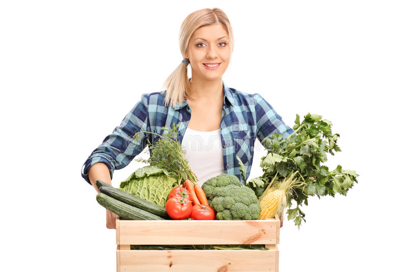 Het vrouwelijke landbouwer stellen achter een krat met groenten stock afbeeldingen
