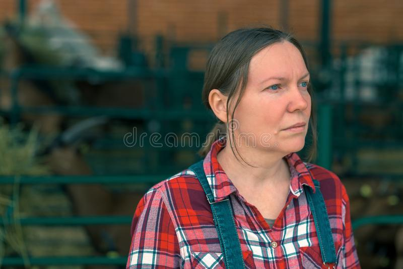 Het vrouwelijke landbouwer stellen op geitlandbouwbedrijf stock fotografie