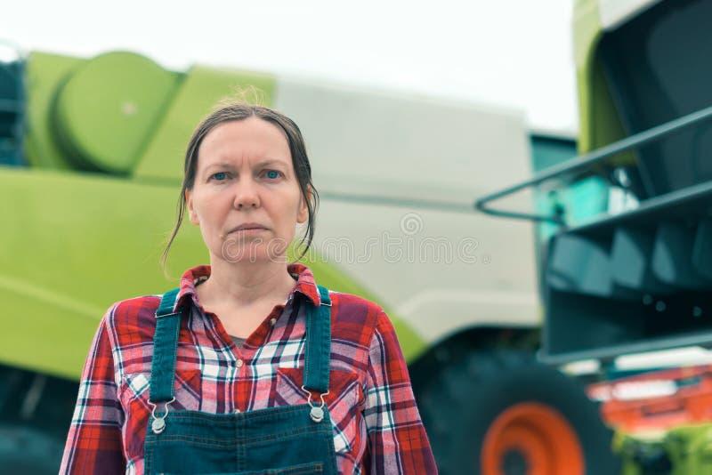 Het vrouwelijke landbouwer stellen voor maaidorser stock afbeeldingen