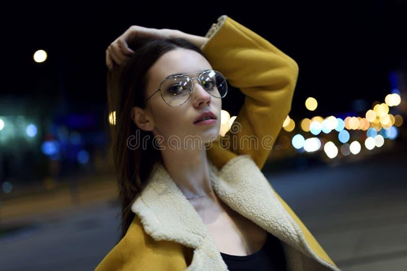 Het vrouwelijke model stellen in geel jasje en grote die glazen, door de lichten van het stadscentrum wordt aangestoken Modieuze  stock afbeelding