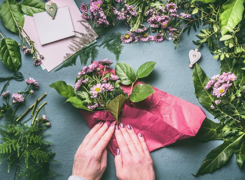 Het vrouwelijke mooie boeket van de handomslag van roze bloemen in verpakkend document op bloemistwerkruimte, hoogste mening stock fotografie