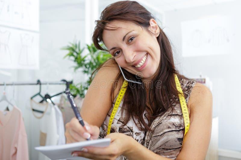 Het vrouwelijke naaister nemen neemt van terwijl het spreken op telefoon nota royalty-vrije stock afbeeldingen
