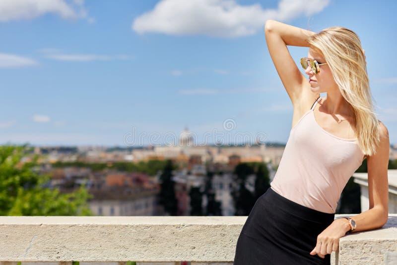 Het vrouwelijke ontspannen die zich bij balkon bevinden royalty-vrije stock foto's