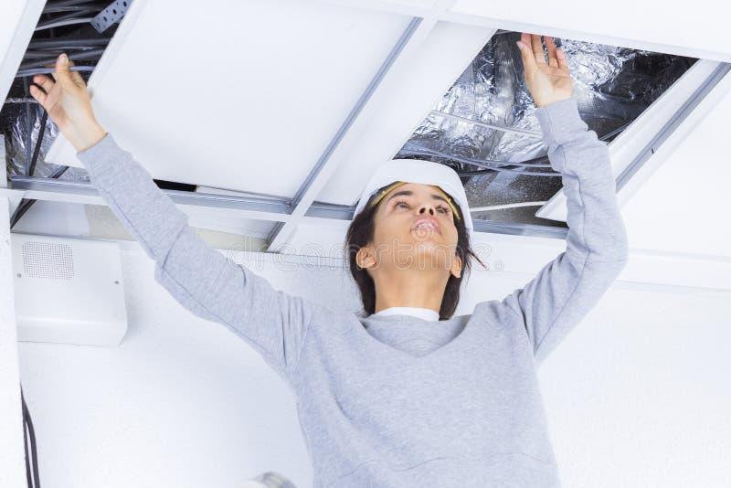 Het vrouwelijke Plafond van Elektricieninstalling lights in stock foto's