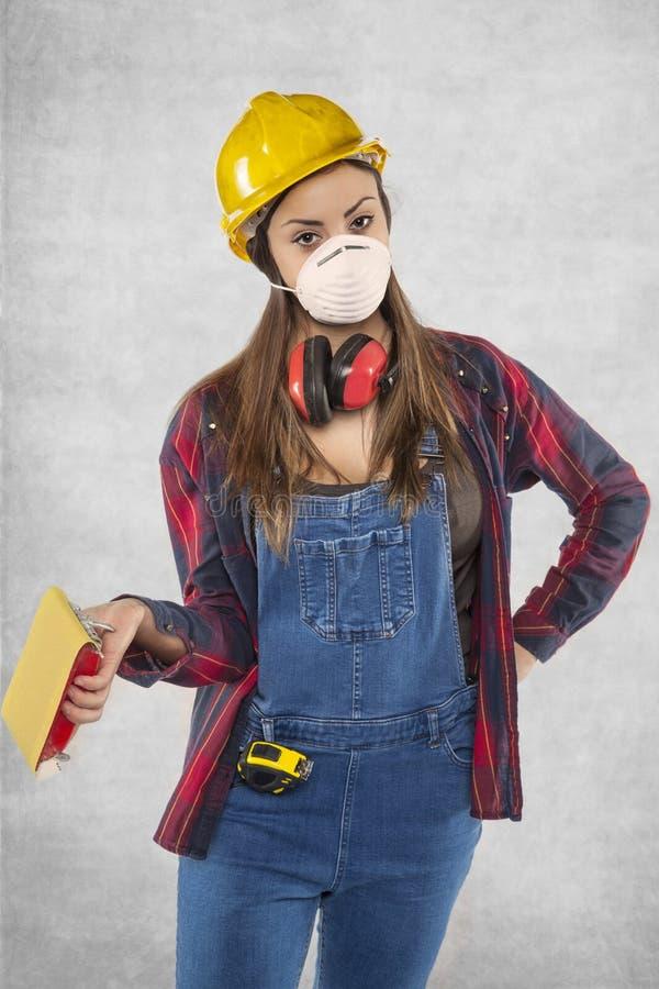 Het vrouwelijke schuurpapier van de bouwvakkerholding stock foto