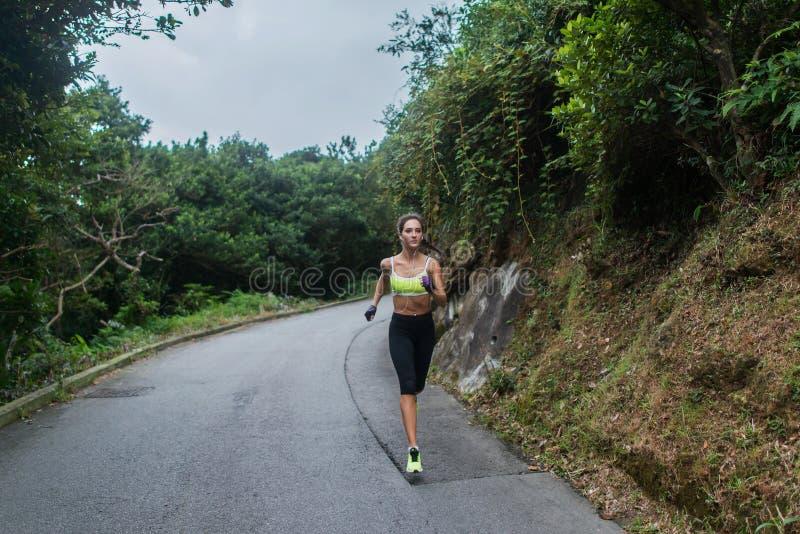 Het vrouwelijke sport model lopen op weg in bergen Geschiktheidsvrouw die in openlucht opleiden royalty-vrije stock afbeeldingen