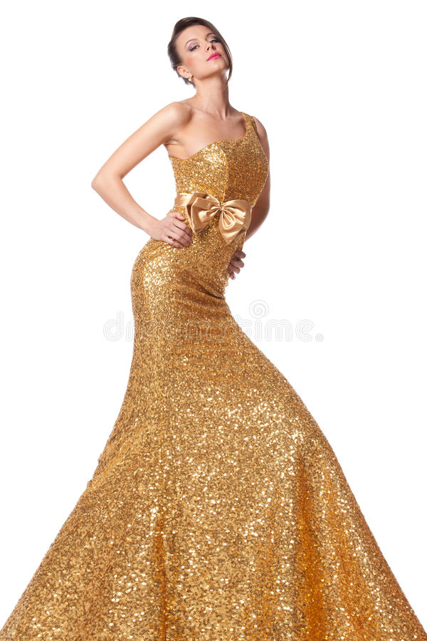Het vrouwelijke stellen in lange gouden kleding stock afbeelding