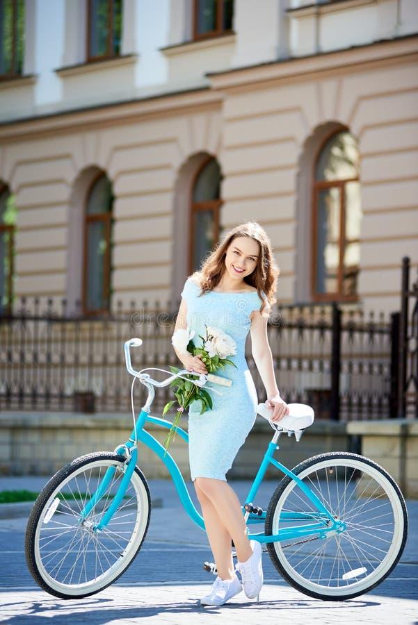 Het vrouwelijke stellen met pioenen dichtbij uitstekende fiets die camera bekijken royalty-vrije stock fotografie
