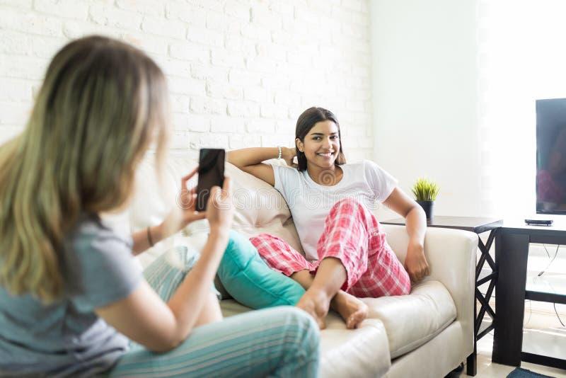Het vrouwelijke Stellen terwijl Vriend die op Sofa During Pajama P fotograferen stock afbeelding