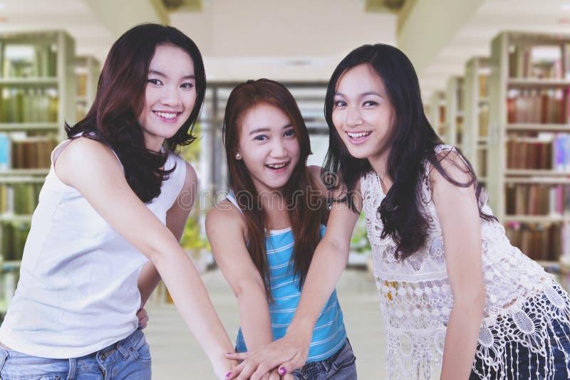 Het vrouwelijke studenten toetreden dient de bibliotheek in royalty-vrije stock foto