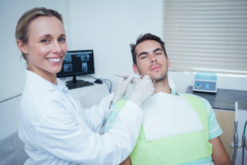 Het vrouwelijke tandarts onderzoeken bemant tanden stock foto