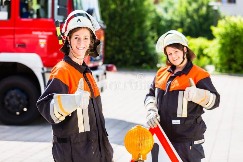 Het vrouwelijke teken van de de vestigingsaandacht van brandvechters stock afbeelding