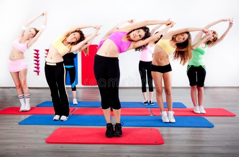 Het vrouwelijke uitrekken zich in een klasse van de aerobicsoefening royalty-vrije stock afbeelding