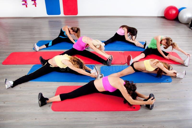 Het vrouwelijke uitrekken zich in een klasse van de aerobicsoefening stock afbeeldingen