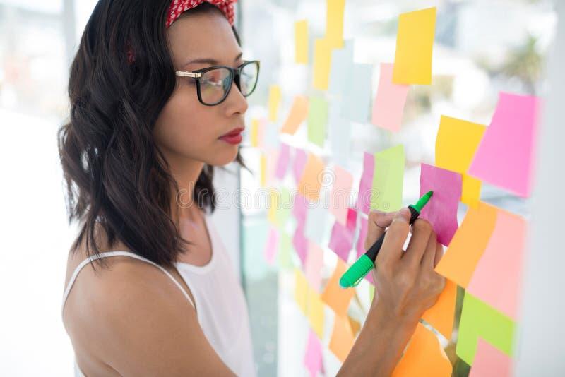 Het vrouwelijke uitvoerende schrijven op kleverige nota's stock afbeelding