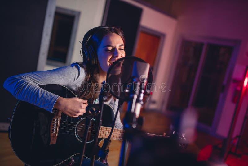 Het vrouwelijke vocale kunstenaar zingen in een opnamestudio royalty-vrije stock afbeelding