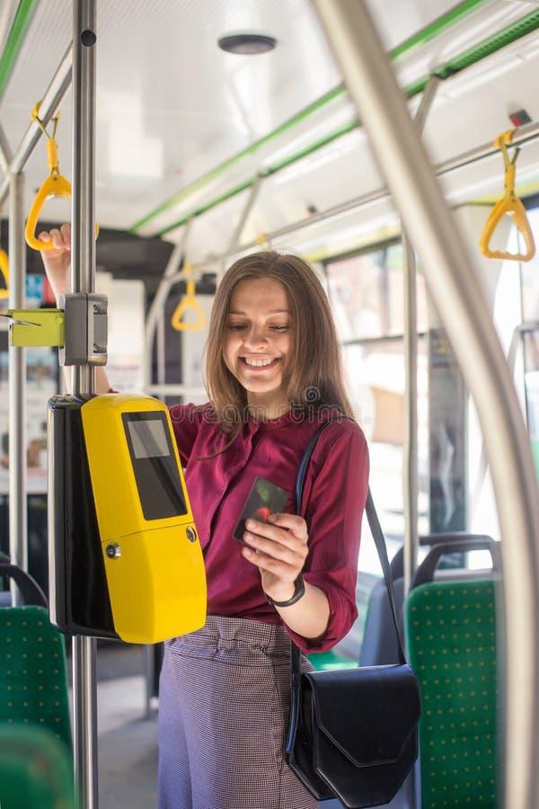 Het vrouwelijke Vrouw betalen conctactless met smartphone voor het openbare vervoer in de tram stock afbeelding