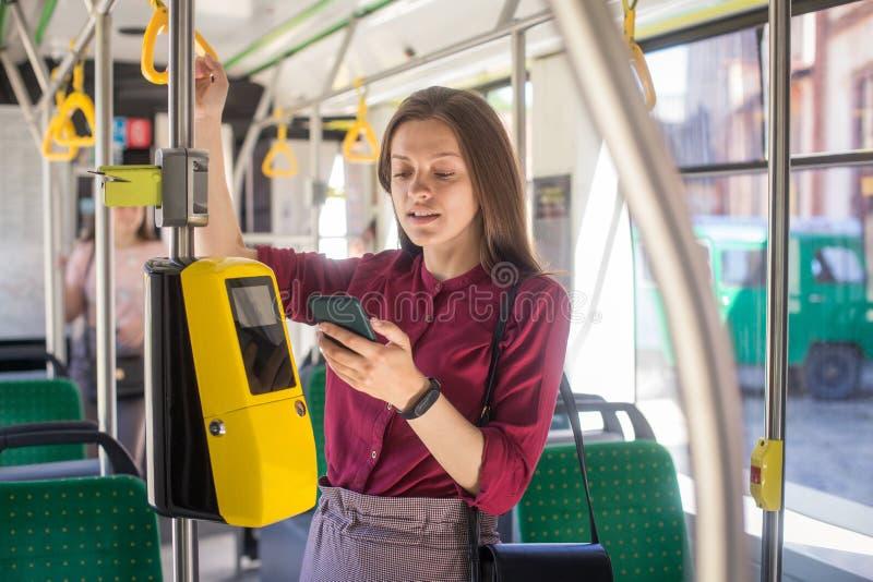 Het vrouwelijke Vrouw betalen conctactless met smartphone voor het openbare vervoer in de tram stock afbeeldingen