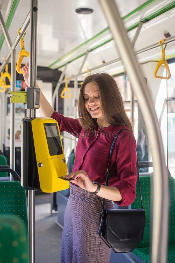 Het vrouwelijke Vrouw betalen conctactless met smartphone voor het openbare vervoer in de tram stock fotografie